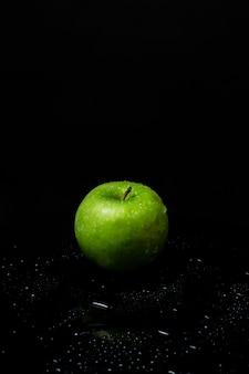 Pomme verte fraîche sur fond noir
