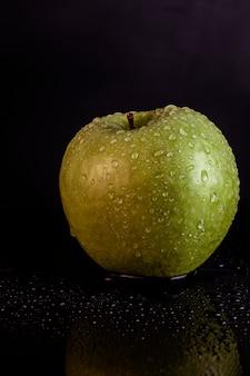 Pomme verte avec des gouttes d'eau sur fond noir