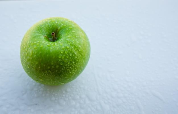 Pomme verte humide sur blanc, vue grand angle.