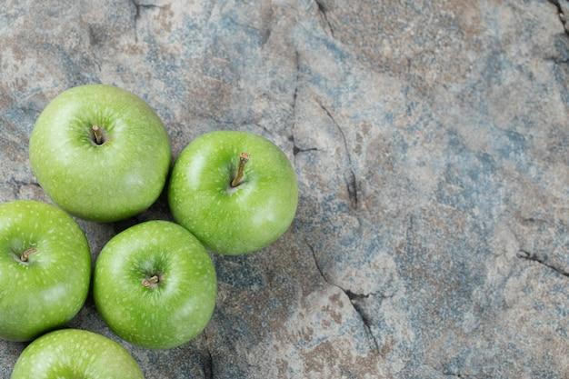 Pomme verte isolée sur béton.