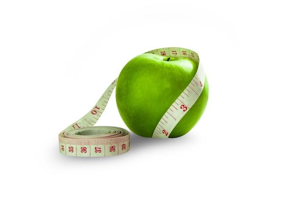 Pomme verte isolée enroulée autour d'un ruban à mesurer