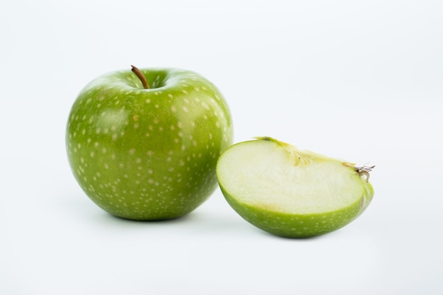 Pomme verte juteuse coupe moelleuse isolé sur blanc