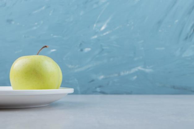 Pomme verte juteuse sur plaque blanche