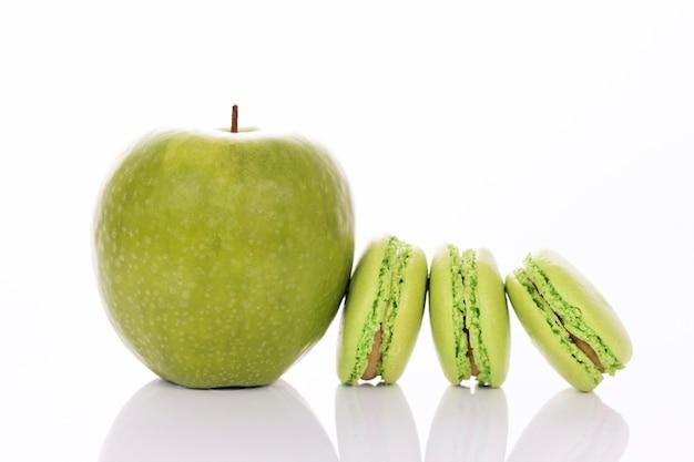 Pomme verte avec des macarons sur fond blanc
