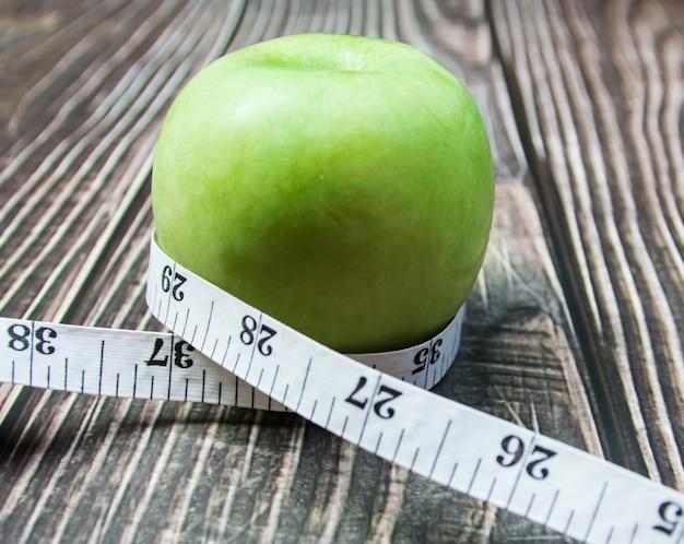 Pomme verte avec mesure sur le bois