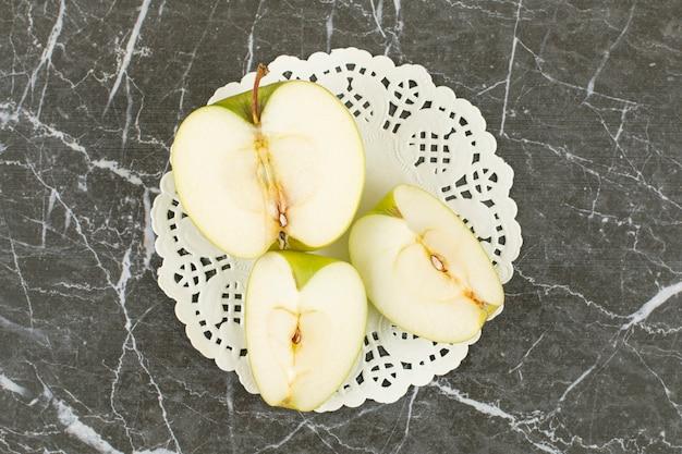 Pomme verte à moitié coupée et tranchée. pomme verte bio sur gris.