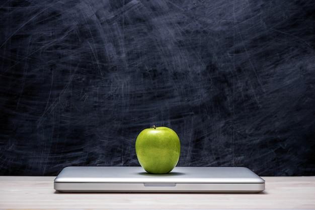 Pomme verte sur ordinateur portable sur table devant le tableau.