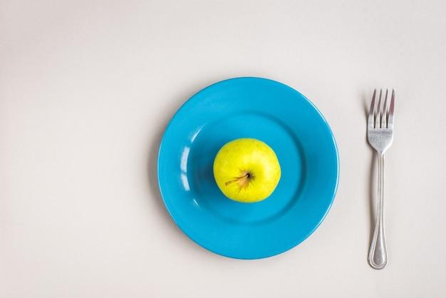 Pomme verte sur pomme bleue sur mur gris. concept de régime.