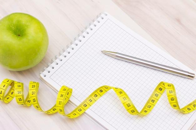 Pomme verte, un ruban à mesurer, un cahier pour écrire sur une surface en bois clair. préparation pour la saison estivale et la plage, perte de poids et concept sportif