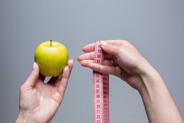 Pomme verte et ruban à mesurer en mains féminines sur mur gris