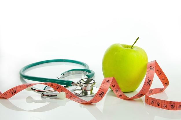 Pomme verte avec ruban à mesurer et stéthoscope isolé