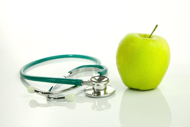 Pomme verte et stéthoscope isolés