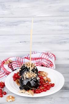 Pommes au caramel sucré sur des bâtons avec des baies, sur une table en bois
