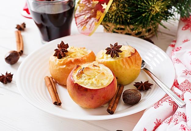 Pommes au four farcies avec du fromage cottage, des raisins secs et des amandes pour noël sur fond blanc.