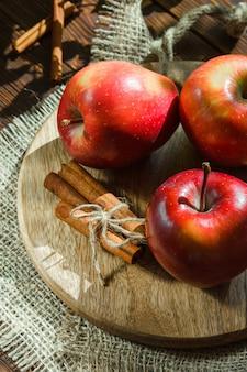 Pommes avec des bâtons de cannelle sur une planche à découper