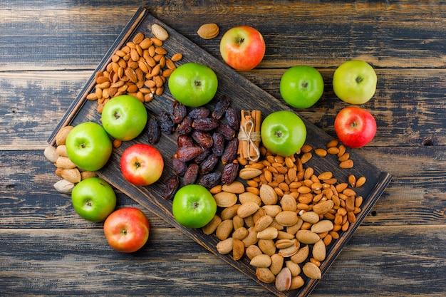 Pommes avec bâtons de cannelle, tas de dattes et amandes vue de dessus sur planche de bois et bois