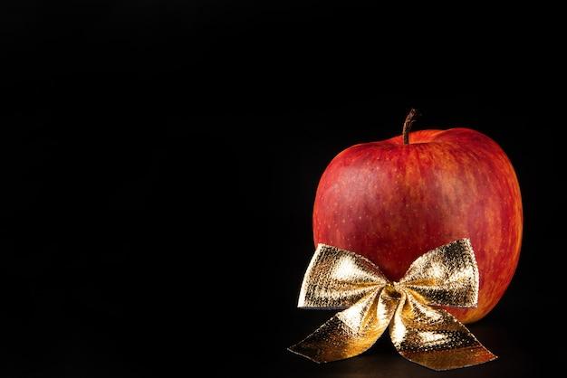 Pommes, belle pomme et un arc doré disposés sur fond noir, portrait discret, mise au point sélective.