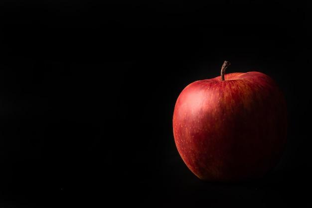 Pommes, une belle pomme disposée sur fond noir, portrait discret, mise au point sélective.