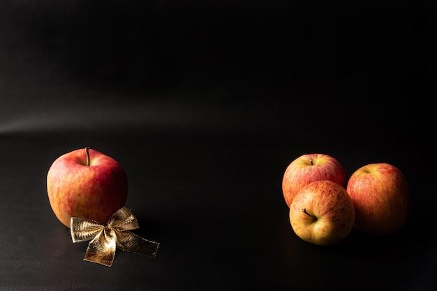 Pommes, belles pommes et arc doré disposés sur fond noir, portrait discret, mise au point sélective.