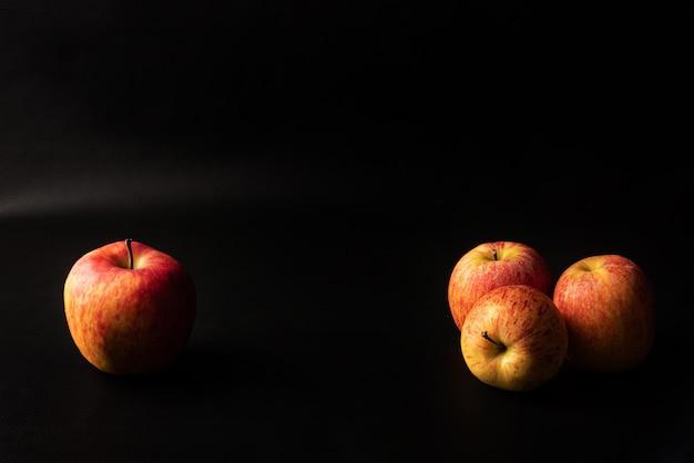 Pommes, belles pommes disposées sur fond noir, portrait discret, mise au point sélective.