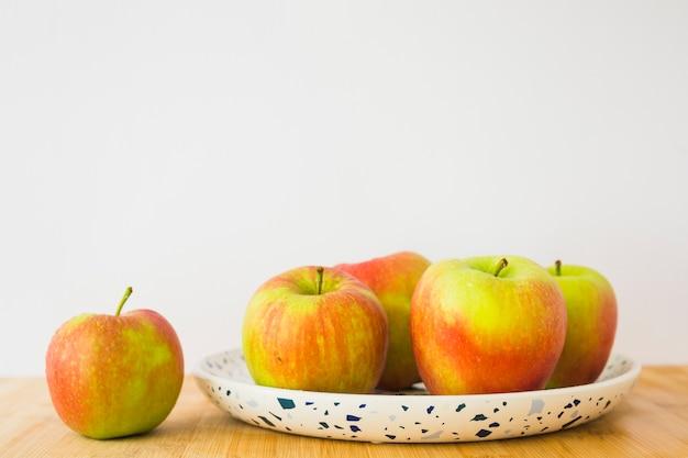 Pommes biologiques fraîches sur plaque sur la table en bois contre blanc