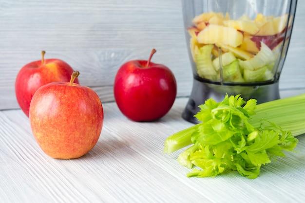 Pommes, une branche de céleri et un robot culinaire sur une table blanche