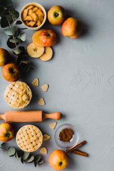Pommes et cannelle près de tartes et rouleau à pâtisserie