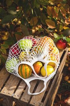 Pommes et citrouilles dans un sac de ficelle sur une boîte rurale dans un jardin