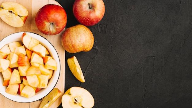 Des pommes coupées et entières sur une planche à découper