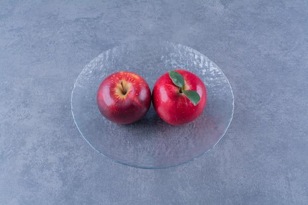 Pommes à croquer sur une plaque de verre sur la surface sombre