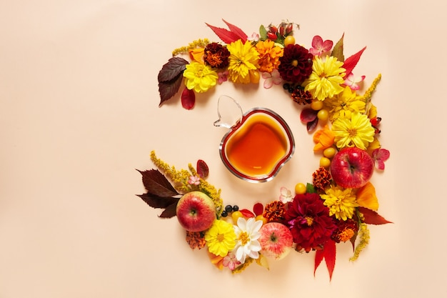 Pommes, dahlia, soucis, fleurs de rudbeckia et miel. concept pour roch hachana le nouvel an juif. vue de dessus, gros plan, copiez l'espace sur fond pastel.