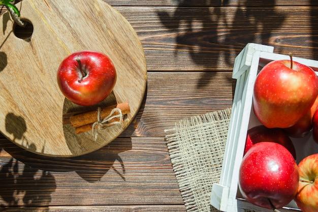 Pommes dans une boîte blanche et pomme avec des bâtons de cannelle sur une planche à découper