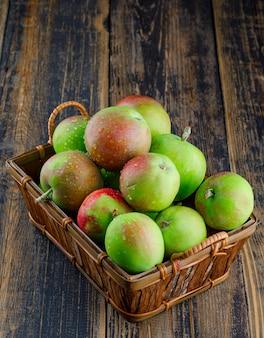 Pommes dans un panier sur fond de bois, vue grand angle.