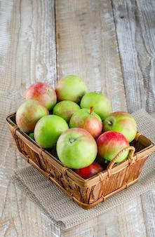 Pommes dans un panier high angle view sur bois et napperon