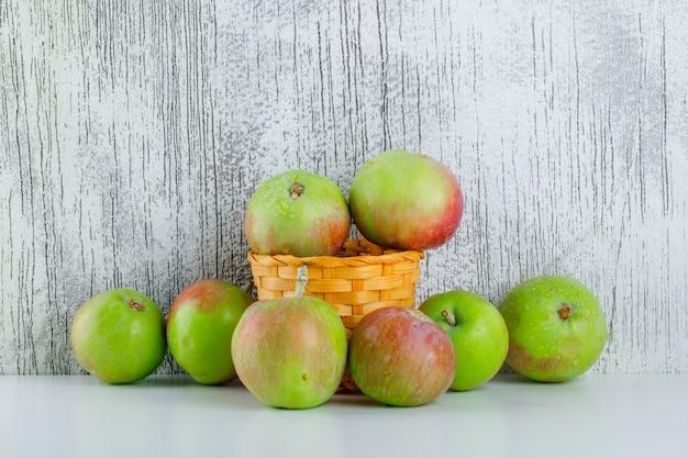 Pommes dans un panier en osier sur blanc et grungy, vue latérale.
