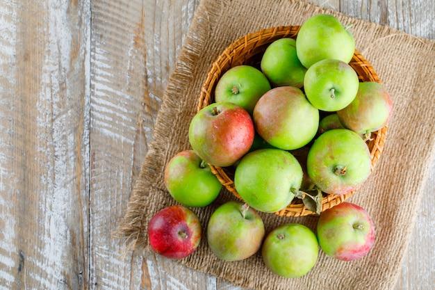 Pommes dans un panier en osier sur bois et morceau de sac.