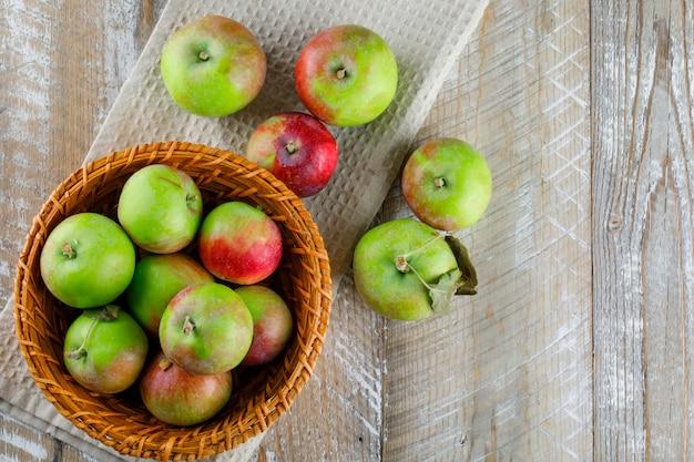 Pommes dans un panier en osier sur bois et torchon de cuisine.
