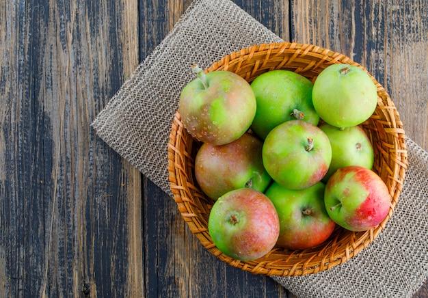 Pommes dans un panier en osier sur fond en bois et napperon. pose à plat.