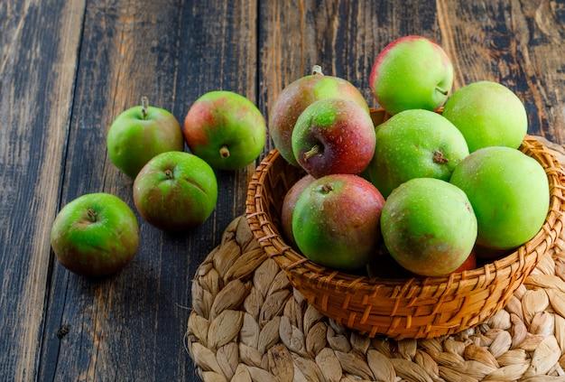 Pommes dans un panier en osier sur fond en bois et napperon. vue grand angle.