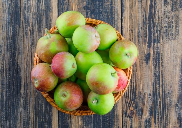 Pommes dans un panier en osier sur un fond en bois. pose à plat.