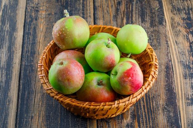Pommes dans un panier en osier sur un fond en bois. vue grand angle.