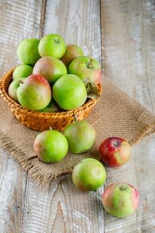 Pommes dans un panier en osier high angle view sur bois et morceau de sac