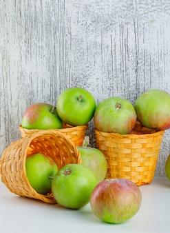 Pommes dans des paniers en osier vue latérale sur blanc et grungy