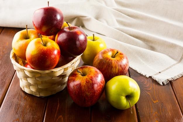 Pommes dans le petit panier en osier sur un fond en bois foncé