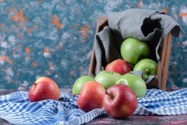 Pommes dans un plateau en bois rustique au sol.
