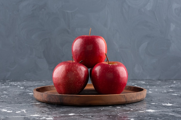 Pommes entières brillantes rouges placées sur une plaque en bois.