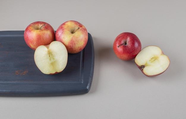 Pommes entières et tranchées sur et à côté d'une planche sur marbre