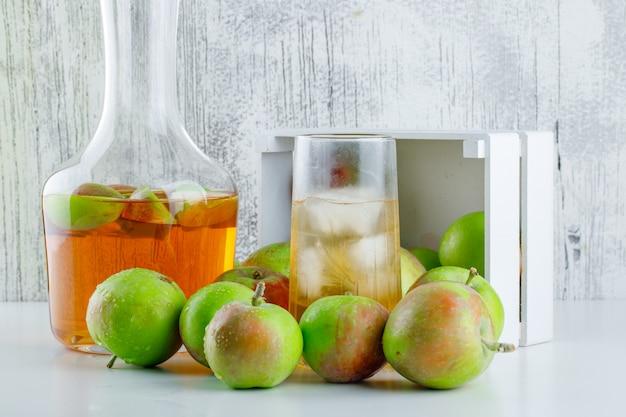 Pommes éparpillées à partir d'une boîte en bois avec vue de côté de boisson sur blanc et grungy