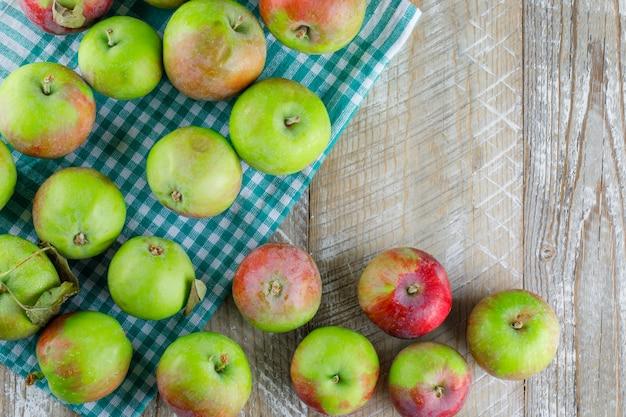 Pommes éparpillées sur tissu en bois et pique-nique. pose à plat.