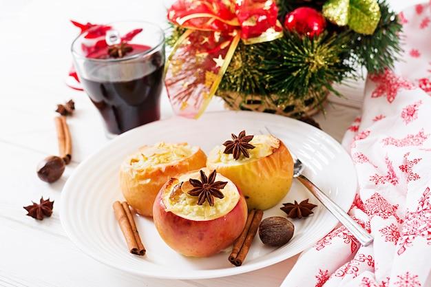 Pommes farcies au four avec du fromage cottage, des raisins secs et des amandes pour noël sur fond blanc. dessert de nourriture de noël.